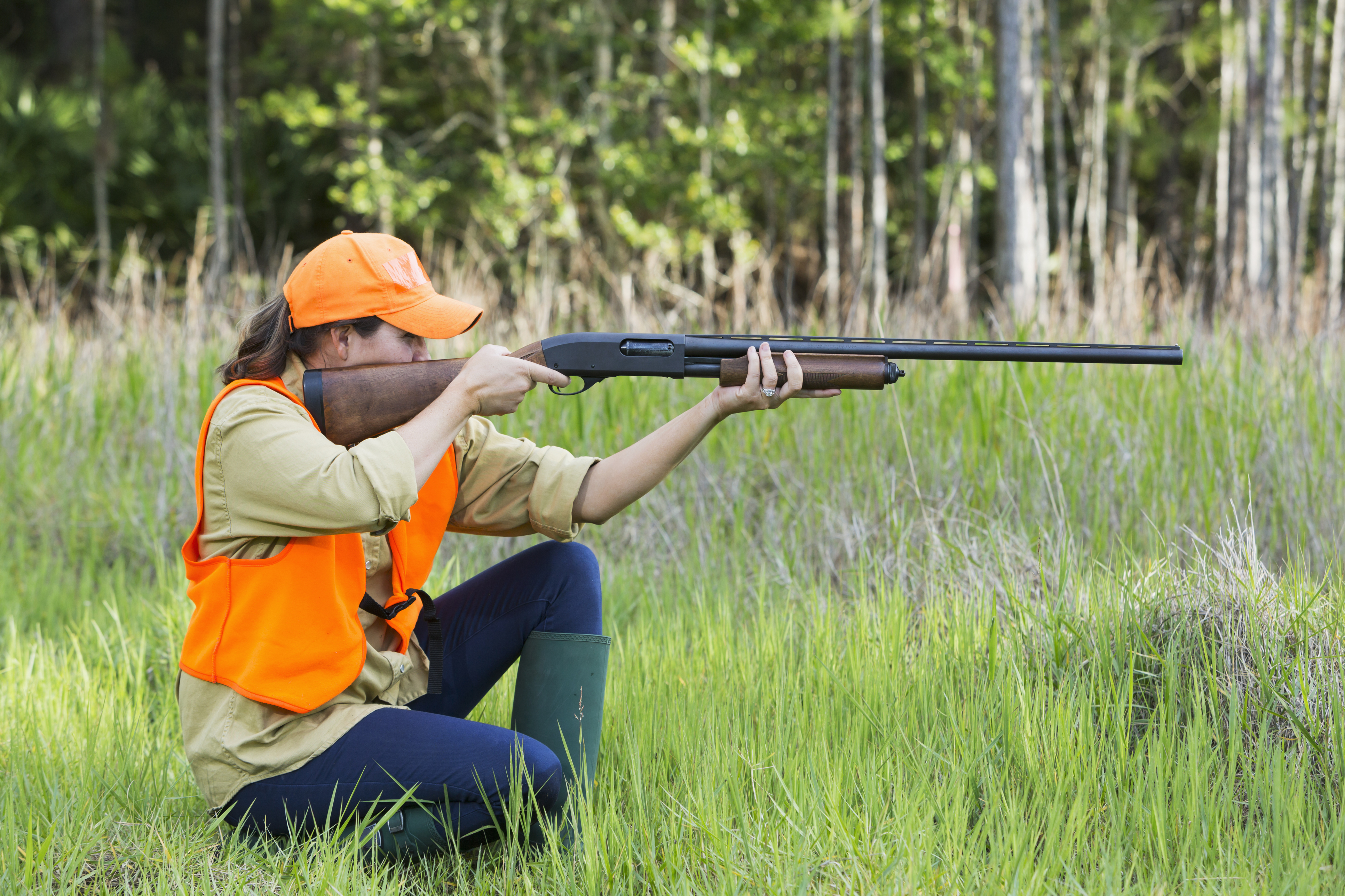 A woman hunting for birds or other small game, kneeling in tall grass, wearing a bright orange safety vest and hat, holding a shotgun, taking aim at her target.